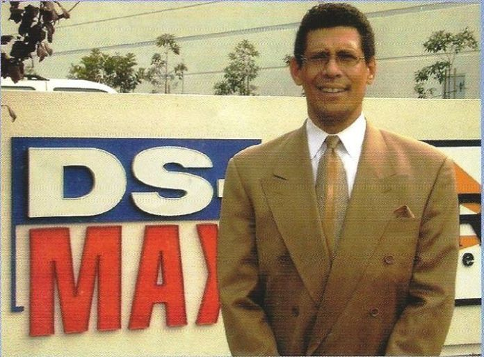 Photo of a younger Murray Reinhart standing in front of the DS-MAX logo.